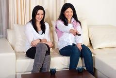 lyckliga hållande ögonen på kvinnor för tv två Royaltyfri Bild