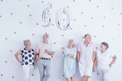 Lyckliga hög ballonger för man- och kvinnainnehavsilver arkivfoto