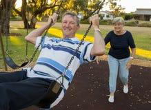 Lyckliga höga amerikanska par omkring 70 år gammalt tycka om på gunga parkerar med den driftiga maken för frun som tillsammans le Royaltyfria Foton