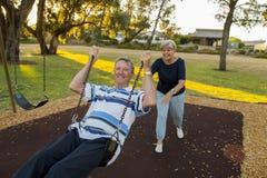 Lyckliga höga amerikanska par omkring 70 år gammalt tycka om på gunga parkerar med den driftiga maken för frun som tillsammans le Arkivbild