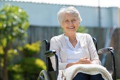 Lyckliga höga kvinnor i rullstol arkivbilder