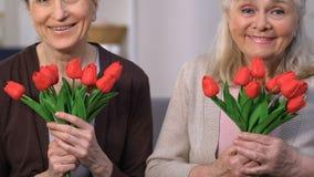 Lyckliga höga kvinnor som luktar härliga blommor, moderdag, framlägger leverans stock video