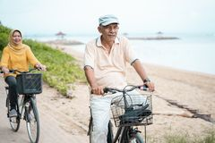 Lyckliga höga muslim par som övar rida cykeln tillsammans royaltyfri fotografi