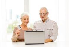 Lyckliga höga par med bärbara datorn och kreditkorten Royaltyfria Bilder