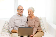 Lyckliga höga par med den hemmastadda bärbara datorn Arkivfoton