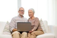 Lyckliga höga par med den hemmastadda bärbara datorn Fotografering för Bildbyråer