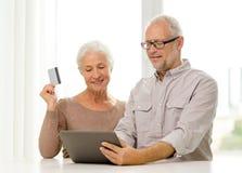 Lyckliga höga par med den minnestavlaPC och kreditkorten Royaltyfria Foton