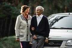 Lyckliga höga par med den nya bilen royaltyfri foto
