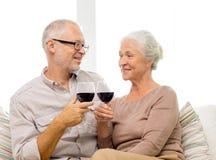 Lyckliga höga par med exponeringsglas av rött vin Royaltyfria Foton