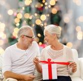 Lyckliga höga par med gåvaasken hemma Arkivbilder