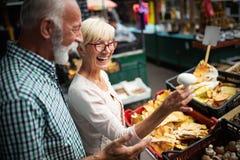 Lyckliga höga par med korgen på den lokala marknaden royaltyfria foton