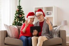 Lyckliga höga par med minnestavlaPC på jul Fotografering för Bildbyråer