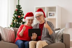 Lyckliga höga par med minnestavlaPC på jul Royaltyfri Bild