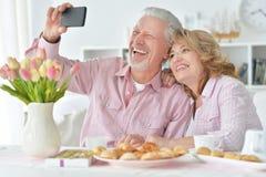 Lyckliga höga par med smartphonen som dricker te arkivbilder
