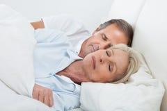 Lyckliga höga par på att sova säng Royaltyfri Fotografi