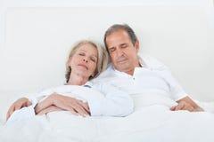 Lyckliga höga par på att sova säng Royaltyfri Bild