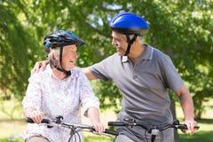Lyckliga höga par på deras cykel Arkivbilder