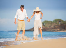Lyckliga höga par på stranden. Avgång lyxig tropisk Res arkivfoto