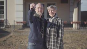 Lyckliga höga par, skallig man och kvinna med grått kort hår i lag- och halsdukställning nära hus och mannen som visar en tangent lager videofilmer