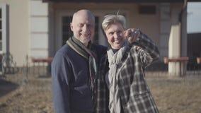 Lyckliga höga par, skallig man och kvinna med grått kort hår i lag- och halsdukställning nära hus Kvinna som in visar en tangent arkivfilmer
