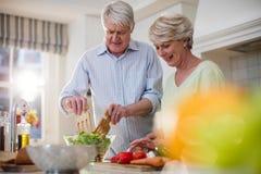 Lyckliga höga par som förbereder grönsaksallad Royaltyfri Bild
