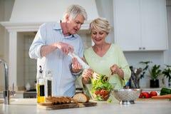 Lyckliga höga par som förbereder grönsaksallad Arkivfoto