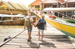 Lyckliga höga par som går den hållande handen på den Koh Panyi muslimfloen royaltyfri fotografi