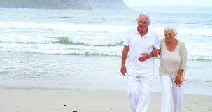 Lyckliga höga par som går på stranden arkivfilmer