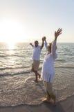 Lyckliga höga par som går rymma den tropiska stranden för händer Royaltyfri Fotografi