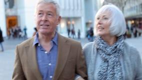 Lyckliga höga par som går till och med utomhus- shoppa område lager videofilmer