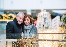 Lyckliga höga par som gör jul som tillsammans shoppar fotografering för bildbyråer