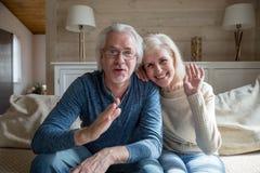 Lyckliga höga par som har den videopd appellen som hemifrån talar royaltyfria bilder