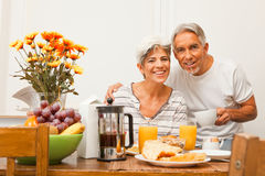 Lyckliga höga par som har frukosten Arkivfoton