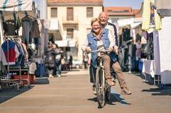 Lyckliga höga par som har gyckel med cykeln på loppmarknaden Royaltyfri Foto