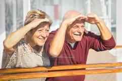 Lyckliga höga par som har gyckel som ser till framtida resor arkivbilder
