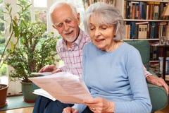 Lyckliga höga par som hemma granskar finanser Fotografering för Bildbyråer