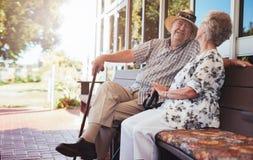 Lyckliga höga par som kopplar av på bänk utanför deras hus Arkivfoton