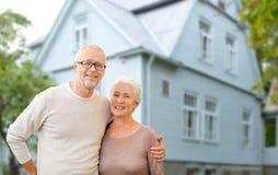 Lyckliga höga par som kramar över husbakgrund fotografering för bildbyråer