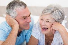 Lyckliga höga par som ligger på säng Fotografering för Bildbyråer