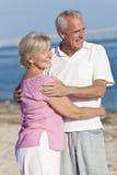 Lyckliga höga par som omfamnar på strand Arkivbild