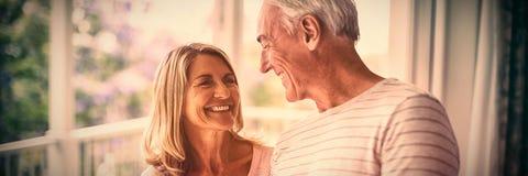 Lyckliga höga par som påverkar varandra med de i balkong arkivbild