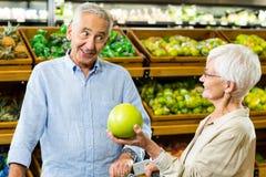 Lyckliga höga par som ser en frukt Arkivfoton