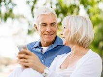Lyckliga höga par som ser smartphonen Arkivbilder