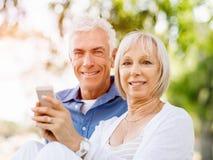 Lyckliga höga par som ser smartphonen fotografering för bildbyråer