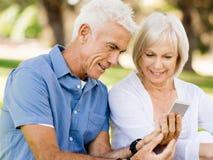 Lyckliga höga par som ser smartphonen royaltyfri bild