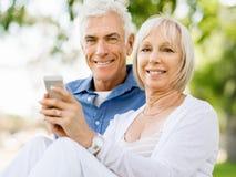 Lyckliga höga par som ser smartphonen royaltyfri fotografi