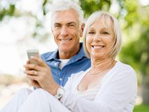 Lyckliga höga par som ser smartphonen royaltyfri foto
