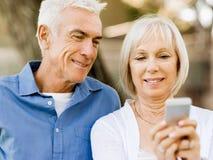 Lyckliga höga par som ser smartphonen arkivfoton