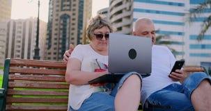 Lyckliga höga par som sitter på en bänk i sommaren i en modern stad med en bärbar dator på bakgrunden av skyskrapor stock video