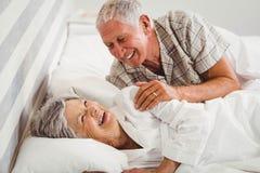 Lyckliga höga par som skrattar på säng Royaltyfri Bild